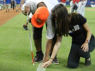 Summer camp student Frankie Young touches the grass along the first baseline with transition summer camp coordinator Emily Nostro.