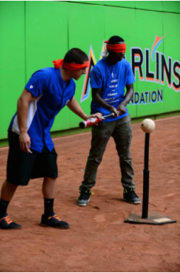 Miami Lighthouse summer camp student batting guided by a Marlins intern
