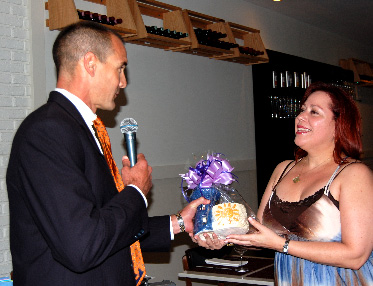 YPOL Co-Chair Agustin Arellano, Jr. presenting Angelique Euro Café co-owner Yolanda Rossi with a Lighthouse ceramic made by Miami Lighthouse Social Group Activities clients