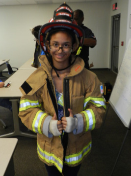 Miami Lighthouse summer camp student wearing a firefighter jacket and hat