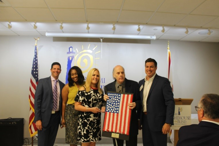 Miami Lighthouse Senior Group Activities client Victor and YPOL Co-Chair Alex Suarez presents handmade American Flag to luncheon sponsor AT&T represented by Cristal Cole, Thais Asper and Alex Dominguez